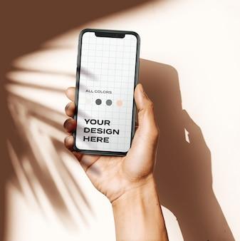 Mockup de mano sosteniendo teléfono inteligente