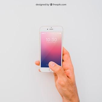 Mockup de mano sujetando smartphone