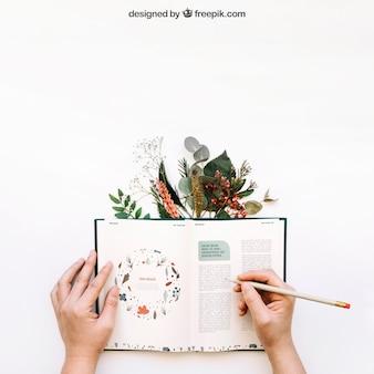 Mockup de manos escribiendo en libro