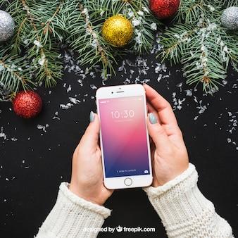 Mockup de manos sujetando smartphone con diseño de navidad