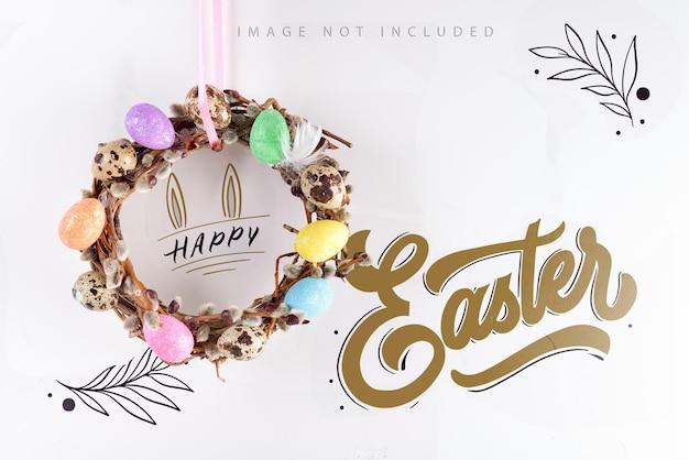 Mockup paaskrans handgemaakt van lente takken van wilg versierd met geschilderde kleurrijke eieren hangt