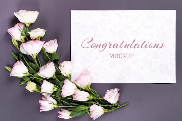 Mockup papier en bloemen op grijs papier