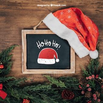 Mockup de pizarra y gorro de santa claus con diseño de navidad