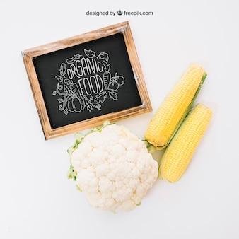 Mockup con pizarra, maíz y coliflor
