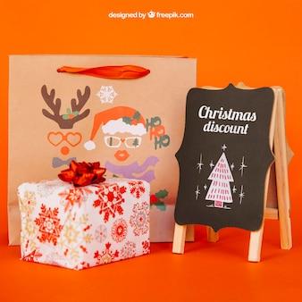 Mockup de pizarra y regalos con diseño de navidad