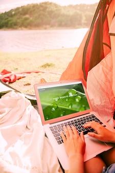 Mockup de portátil con concepto de acampar en naturaleza