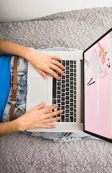 Mockup portatile sul letto con le mani