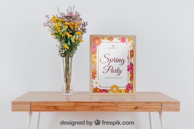 Mockup de primavera con marco y jarrón de flores sobre mesa
