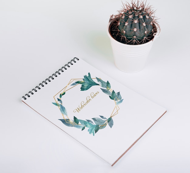 Mockup primaveral de libreta con cactus decorativo