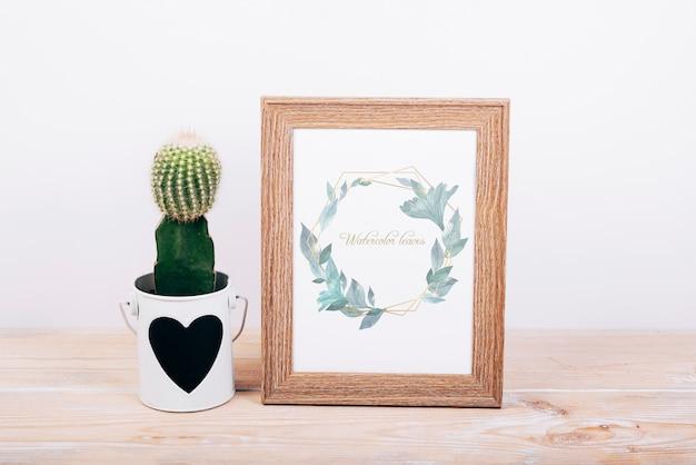 Mockup primaveral con marco de madera y cactus