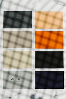 Mockup quadrati di carta colorata campione su un tavolo di marmo