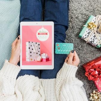 Mockup de rebajas de navidad con mujer usando tableta