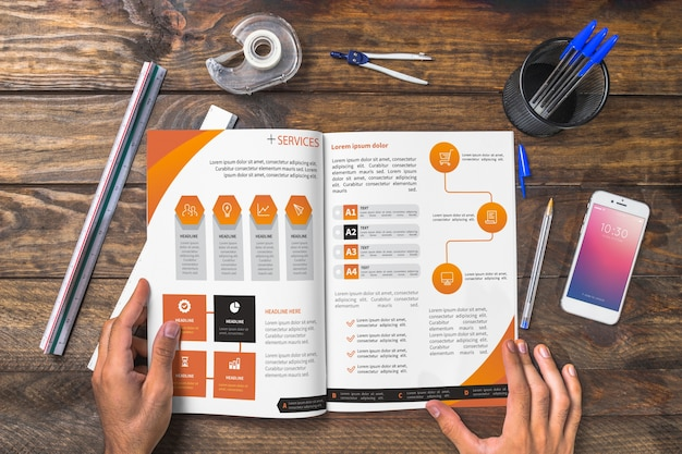 Mockup de revista y smartphone en mesa de madera con bolígrafos y reglas