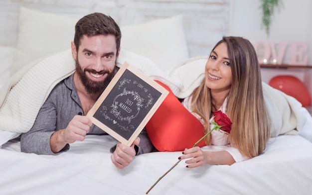 Mockup de san valentin con pareja en cama enseñando pizarra