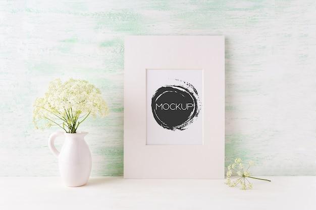 Mockup semplice cornice bianca con teneri fiori selvatici