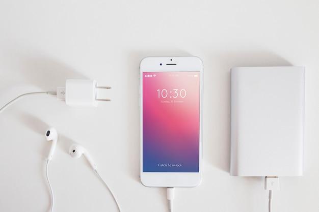 Mockup de smartphone con cable de cargar y auriculares