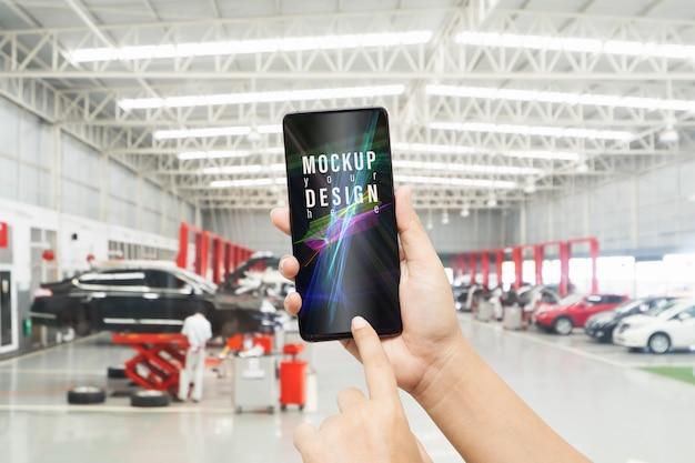 Mockup smartphone in autoreparatiewerkplaats.