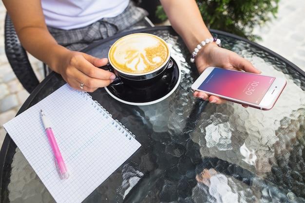 Mockup de smartphone en mesa con café con leche