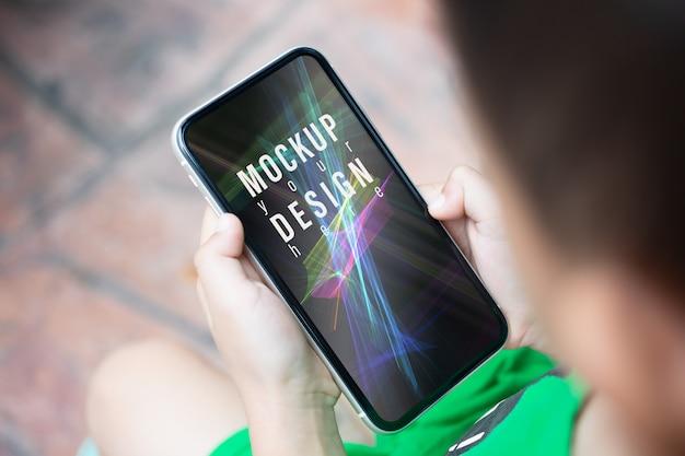 Mockup smartphone met een kleine jongen houden en kijken naar de telefoon