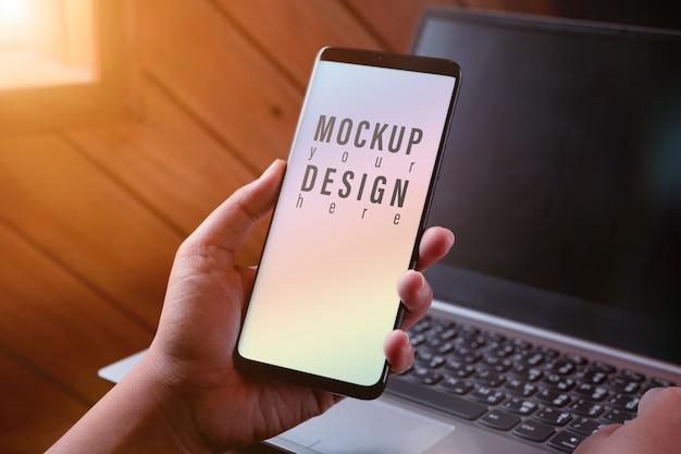 Mockup-smartphonescherm. sluit omhoog handen gebruikend moderne slimme telefoontechnologie met vage laptop