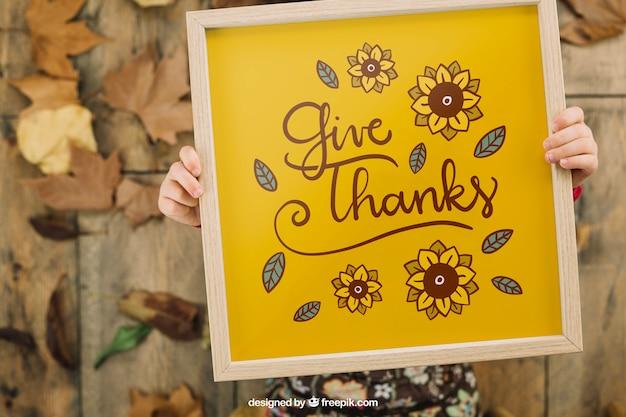 Mockup de thanksgiving con niña sujetando marco