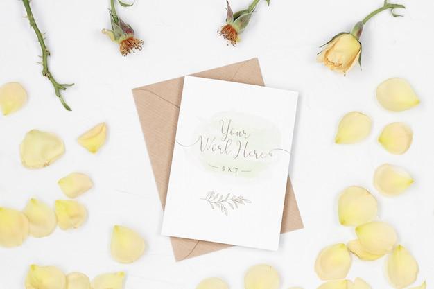 Mockup uitnodigingskaart met ambachtelijke envelop en rozenblaadjes