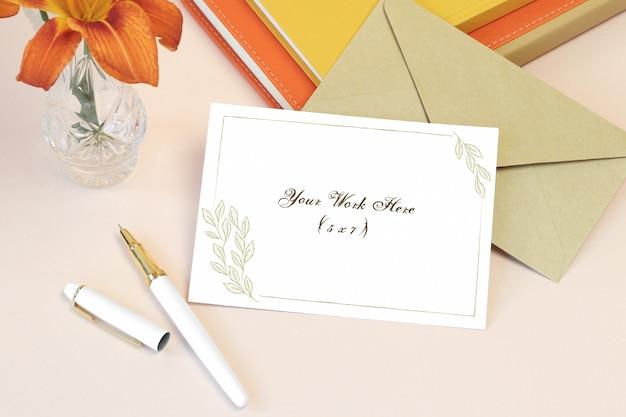 Mockup uitnodigingskaart met boeken en envelop