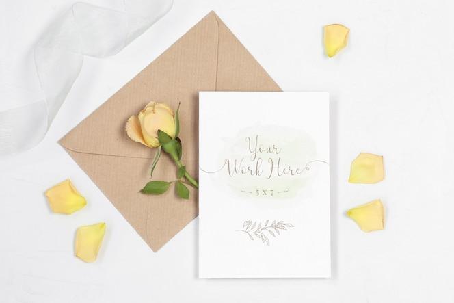 Mockup uitnodigingskaart met envelop, roos en bloemblaadjes