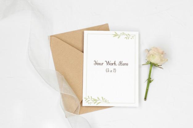 Mockup uitnodigingskaart met envelop, rose en lint
