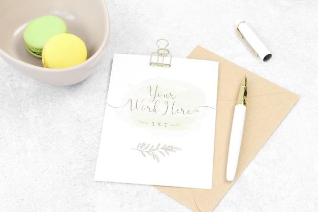 Mockup uitnodigingskaart met pen en macarons