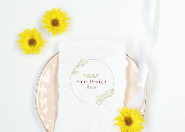 Mockup uitnodigingskaart op roze plaat met gele bloemen