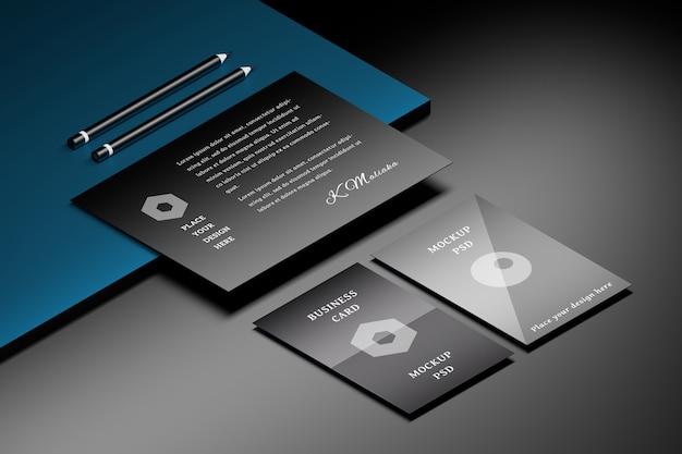 Mockup van a4-vel papier en twee visitekaartjes op zwart blauw oppervlak met twee potloden