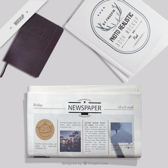 Mockup van de krant met een notebook en fotoboek