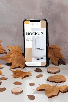 Mockup van de mobiele telefoon die op de tafel staat, omringd door bladeren