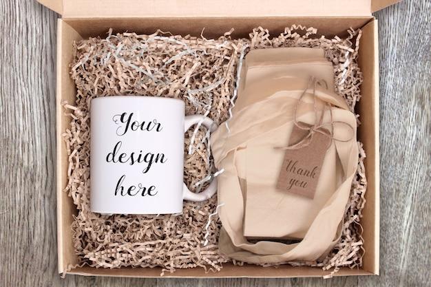 Mockup van een witte keramische koffiemok in doos met papieren zakdoekjes en draagtas