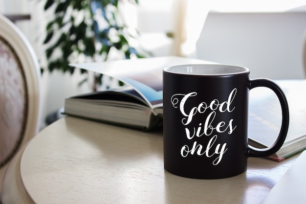 Mockup van een zwarte koffiemok op tafel