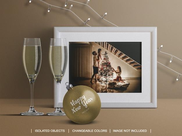 Mockup van het frame van de kerstkaart en kerstmisbal met de decoratie van champagneglazen