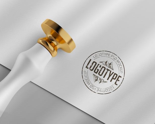 Mockup van papieren logo met gouden ronde rubberen stempel