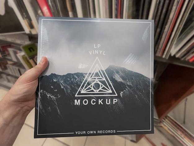 Mockup van vinylplaten albumhoes in de hand houden in vinylwinkel