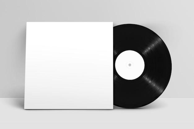 Mockup van vooraanzicht staande blanco vinylplaat met deksel tegen witte muur