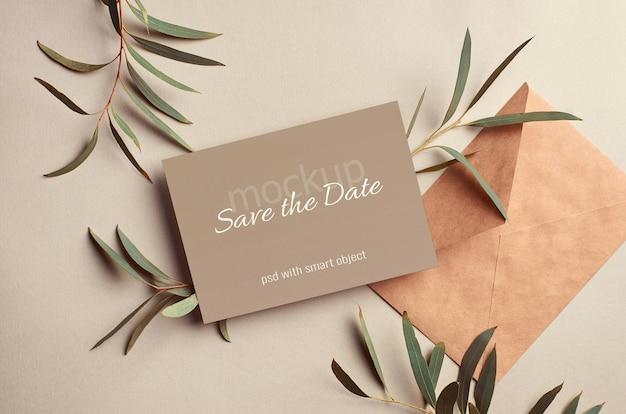 Mockup voor huwelijksuitnodiging met envelop en eucalyptustakjes