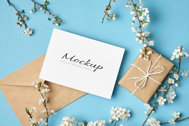 Mockup voor uitnodiging of wenskaart met geschenkdoos, envelop en bloeiende takjes van de kersenboom