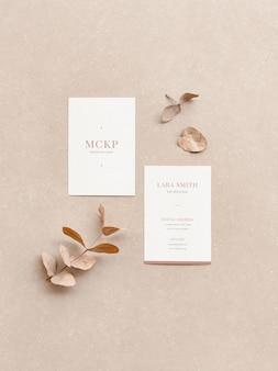 Mockup voor verticale visitekaartjes en bladeren op een gestructureerde achtergrond in platte lay-stijl