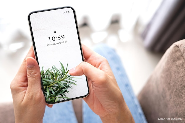 Mockup vrouw hand met de zwarte slimme telefoon met leeg wit scherm op de bank thuis. zakelijk en technologisch concept