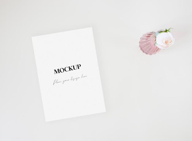 Mockup wenskaart op de beige achtergrond met witte roos in een vaas