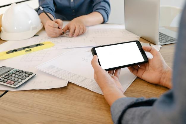 Mockupbeeld van ingenieurs die smartphone gebruiken om ontwerpproject in bureau te trekken