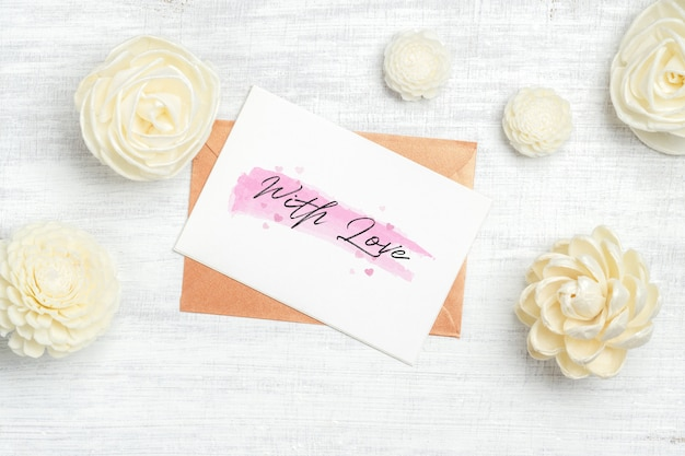 Mockupkaart en envelop op witte hout- en kraftpapier-rozen