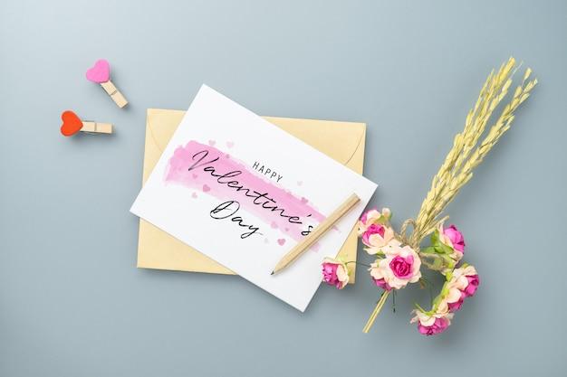Mockupprentbriefkaar en envelop op grijze lijst met ambacht roze bloem.
