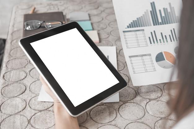Model van dichte omhooggaande bedrijfsvrouw die met tablet en documenten in bureau werken