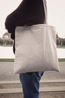 Model van het vrouwelijke model van de straatstad met de zak van het linneneco van de totalisatorstof in openlucht de zomerscène
